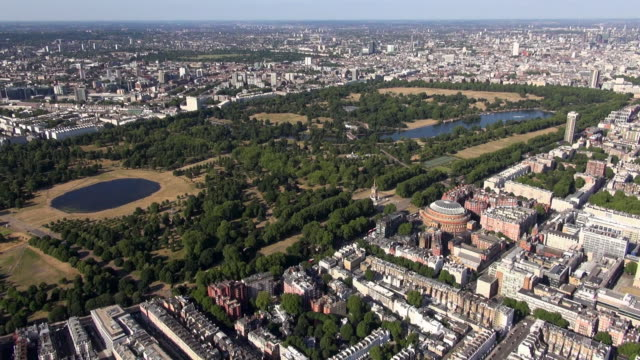 Aerial video panorama of Hyde Park including Round Pond, Kensington Palace and surrounding areas of Knightsbridge with the Royal Albert Hall, Imperial College Queen's Tower and distant views of Paddington and Mayfair
