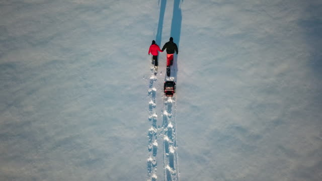 4k aerial video view family snowshoeing outdoor in winter at sunset - standing water stock videos & royalty-free footage