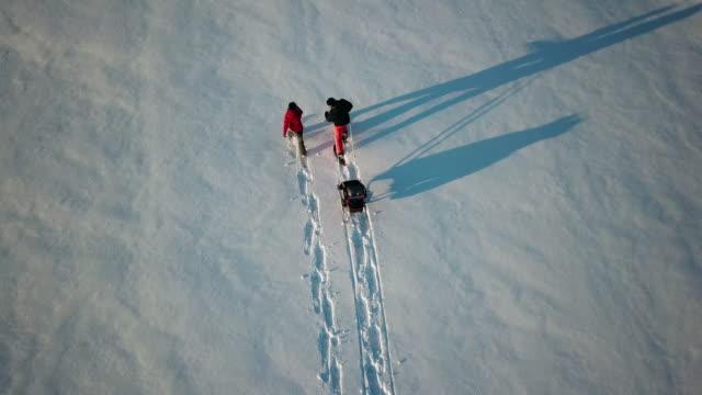 夕暮れ時の冬の屋外スノーシュー 4 k ビデオ空撮家族 - 両親点の映像素材/bロール