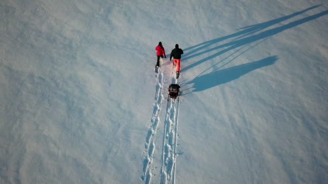 4k aerial video view family snowshoeing outdoor in winter at sunset - footprint stock videos & royalty-free footage
