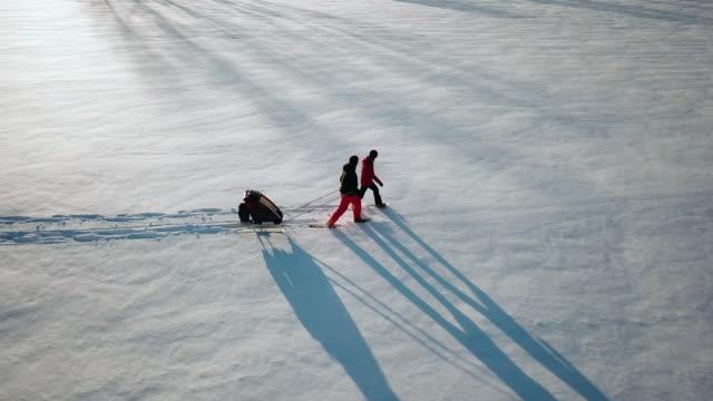vídeos y material grabado en eventos de stock de familia de vista aérea de video de 4 k con raquetas de nieve al aire libre en invierno al atardecer - pisada