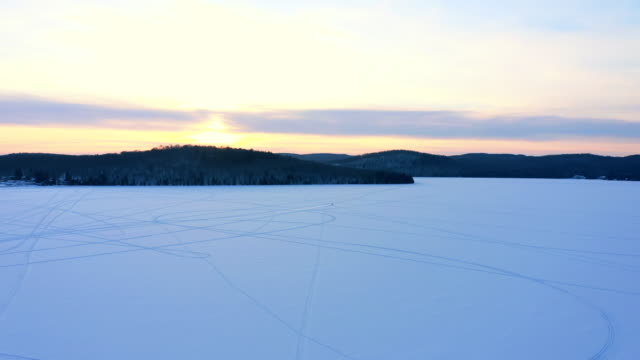 vídeos de stock e filmes b-roll de 4k aerial video view of a lake with snowmobile trace on snow at sunset, quebec, canada - gelo