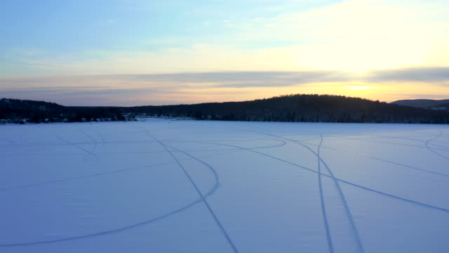 4k aerial video view of a lake with snowmobile trace on snow at sunset, quebec, canada - footpath stock videos & royalty-free footage
