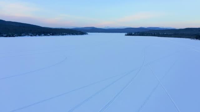 日没時の雪の上にスノーモービルの痕跡を持つ湖の4k航空ビデオビュー, ケベック州, カナダ - ケベック州点の映像素材/bロール