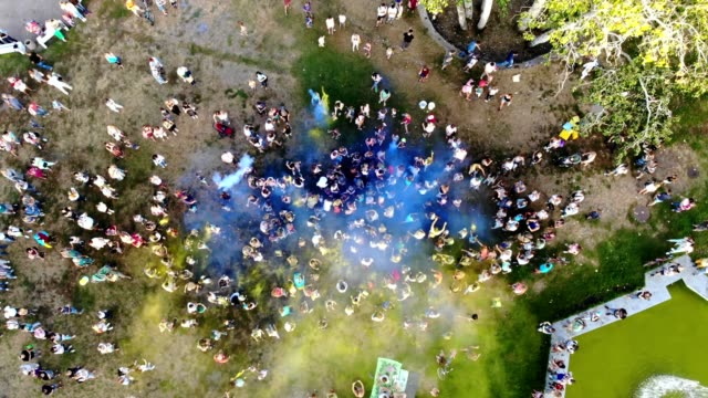 CHERKASY, UKRAINE - AUGUST 24, 2018 : aerial video with drone, Independence Day celebration, festival of colors, people throw up yellow and blue paints in sky, national flag