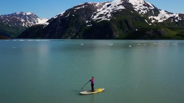 aerial view 360 woman on sup in cove with glacier - using a paddle stock videos & royalty-free footage