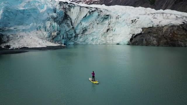 vídeos de stock e filmes b-roll de aerial view 360 woman paddling in cove with glacier - vista de 360 graus