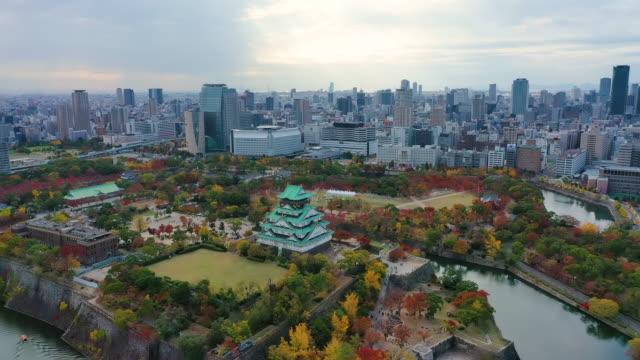 aerial view 4k by drone of osaka castle and building city at osaka, japan - präfektur osaka stock-videos und b-roll-filmmaterial