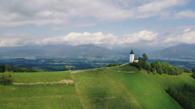 aerial view a small white church on the mountain - slovenia stock videos & royalty-free footage