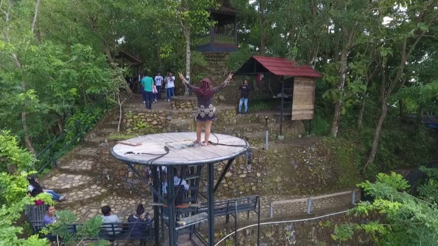 Aerial view a visitor poses for photographs on a platform at the Kalibiru Tourism Village in this aerial video taken at Kulon Progo Regency Special...