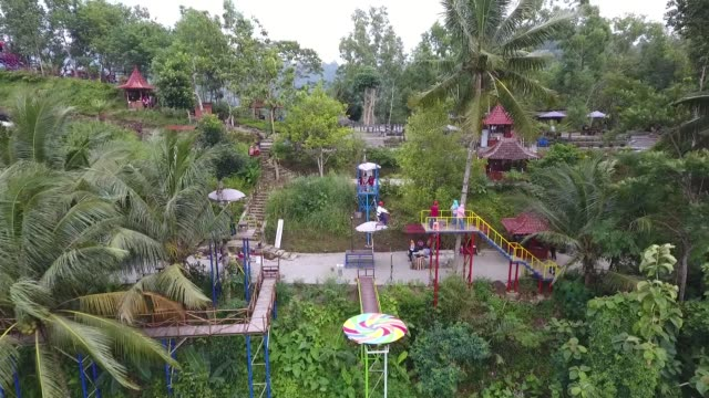 Aerial view a visitor poses for photographs while riding a bicycle on a zipline at the Pule Payung Tourism Hill attraction in this aerial video taken...