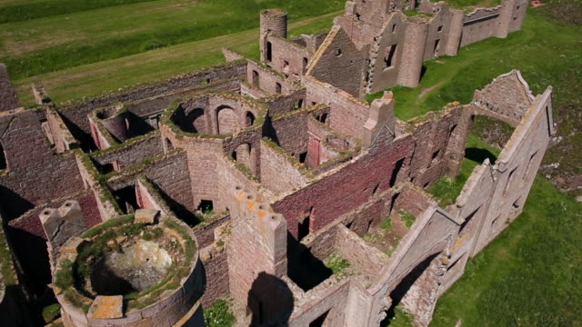 aerial view above new slains castle ruins in aberdeenshire, scotland - castello video stock e b–roll