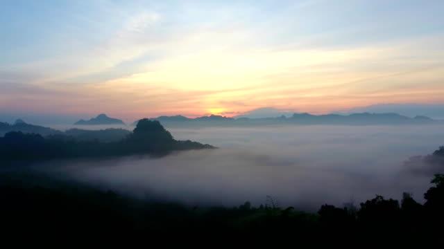 vídeos de stock e filmes b-roll de aerial view above the cloud at sunrise - valley
