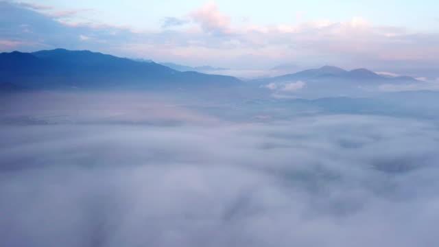 日の出時の山の霧と雲の上の空中ビュー - 静かな情景点の映像素材/bロール