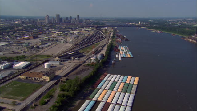 Aerial view along Mississippi River over barges and railyards / downtown area in background / St. Louis, Missouri