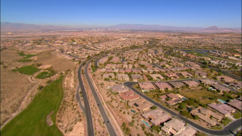aerial view along road running between golf course and housing development / over rows of tract housing - nevada stock videos & royalty-free footage