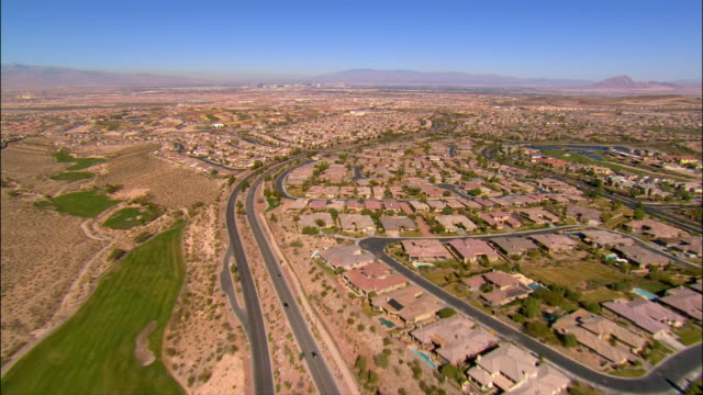 vídeos de stock e filmes b-roll de aerial view along road running between golf course and housing development / over rows of tract housing - nevada
