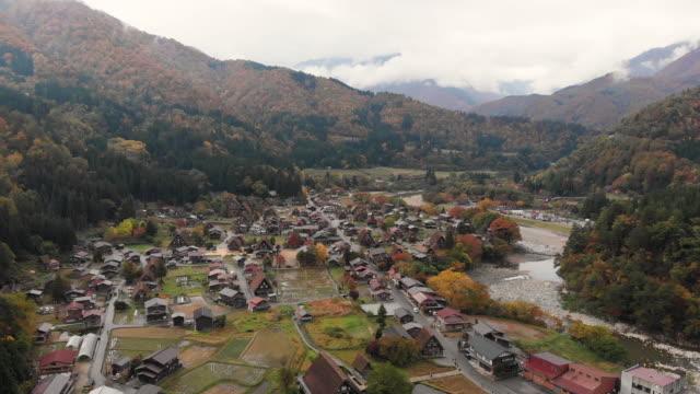 vídeos de stock e filmes b-roll de aerial view and dolly forward of shirakawago village in autumn season, gifu, japan. - telhado de palha