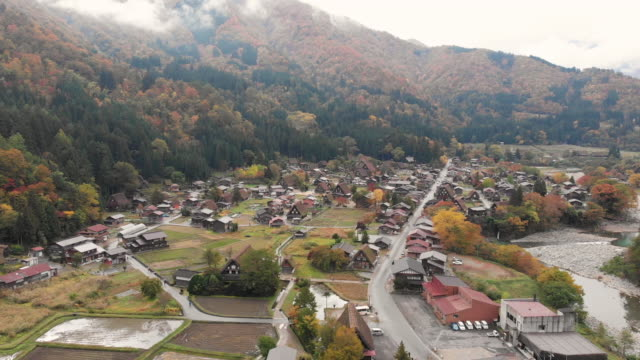 aerial view and dolly left of shirakawago village in autumn season, gifu, japan. - giapponese video stock e b–roll
