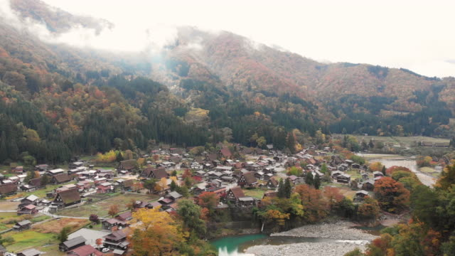 vídeos de stock e filmes b-roll de aerial view and dolly left of shirakawago village in autumn season, gifu, japan. - telhado de palha