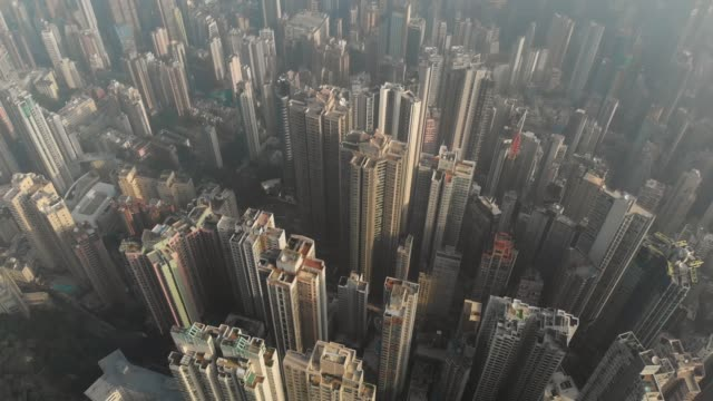 aerial view and dolly left of skyscraper at sunrise in hong kong. - smog stock videos & royalty-free footage