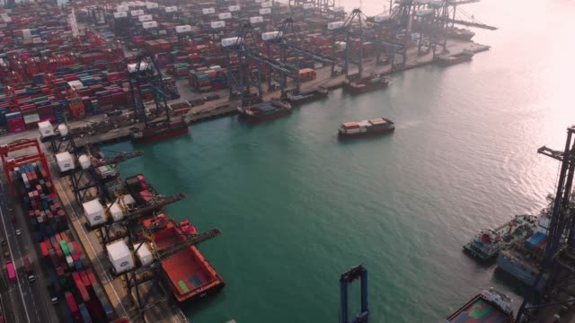 Aerial view and tilt down of Container Ship in Industrial Port.