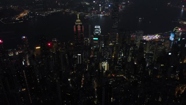 aerial view and tilt down of hong kong skyscraper in night time. - victoria hong kong stock videos & royalty-free footage