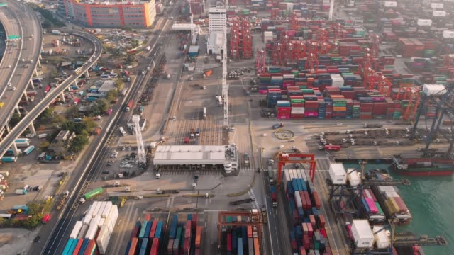aerial view and tilt up of container ship in industrial port. - pier stock videos & royalty-free footage