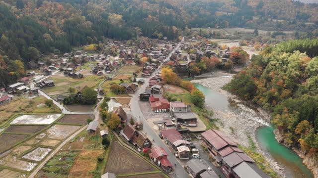 vídeos de stock e filmes b-roll de aerial view and tilt up of shirakawago village in autumn season, gifu, japan. - telhado de palha