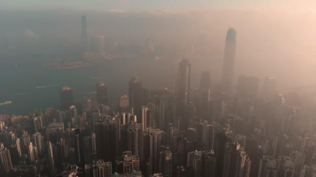 vídeos de stock e filmes b-roll de aerial view and tilt up of skyscraper at sunrise in hong kong. - nevoeiro fotoquímico