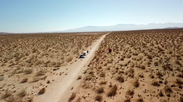 aerial view: angling down towards straight, dirt track in flat, desert landscape - joshua tree national park stock videos & royalty-free footage