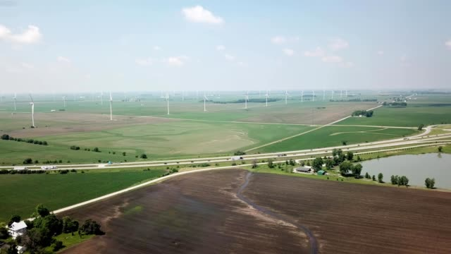 aerial view approaching a windmill farm adjacent to a highway in lafayette indiana - indiana stock videos & royalty-free footage
