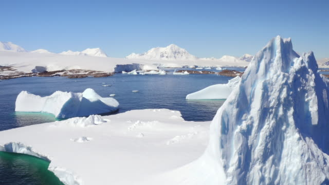 aerial view around a large iceberg in antarctica - antarktis stock-videos und b-roll-filmmaterial