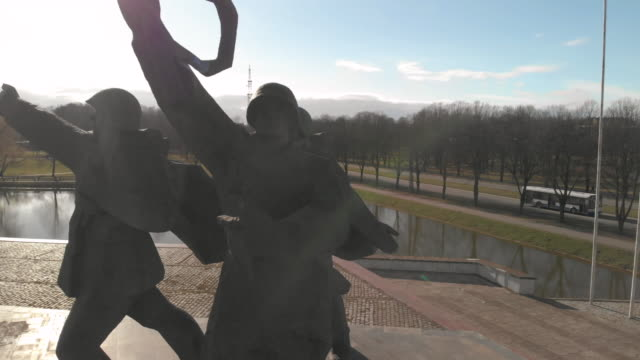 aerial view around victory monument (soldiers with raised riffle and hands) on sunny day in riga. soviet architecture after world war 2 - eternity stock videos & royalty-free footage