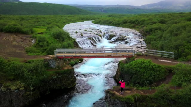 Aerial view Asian woman enjoy view at waterfall in Iceland