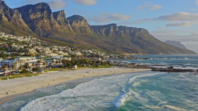 aerial view at beach in camps bay with twelve apostles mountain in the background, cape town, south africa - cape town stock videos & royalty-free footage