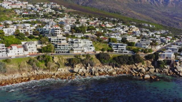 vídeos y material grabado en eventos de stock de vista aérea en la costa en la bahía de campos con un barrio residencial en el fondo, ciudad del cabo, sudáfrica - pared de roca