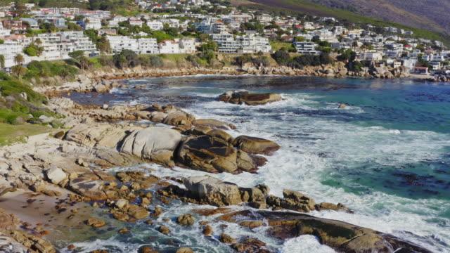 vídeos y material grabado en eventos de stock de vista aérea en la costa en la bahía de campos con doce apóstoles montaña al fondo, ciudad del cabo, sudáfrica - pared de roca