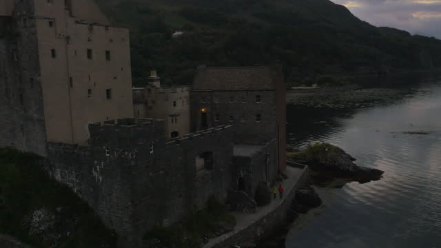 aerial view at dusk eilean donan castle scotland - scottish culture stock videos & royalty-free footage