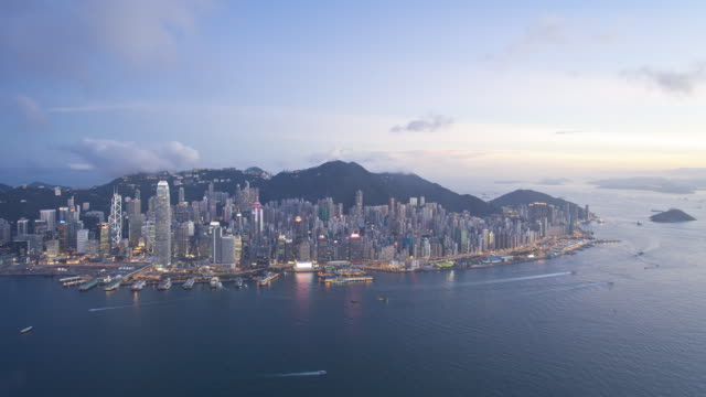 vídeos de stock, filmes e b-roll de aerial view at night over illuminated hong kong island towards victoria peak showing the busy victoria harbour and financial district of central, hong kong, china, time-lapse - victoria peak