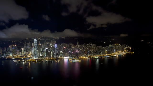 aerial view at night over illuminated hong kong island towards victoria peak showing the busy victoria harbour and financial district of central, hong kong, china, time-lapse - victoria peak stock videos & royalty-free footage