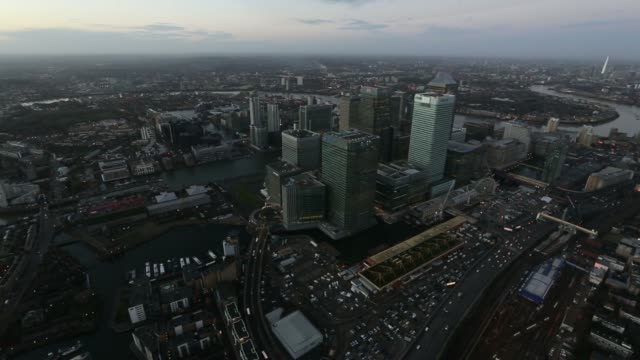 vidéos et rushes de aerial view at sunrise shows no 1 canada square skyscraper offices surrounded by the offices of global financial institutions including hsbc holdings... - entourer