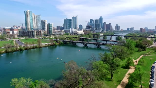 Aerial View Austin Texas Skyline Colorado River Fun Spring water activities going down low near trees with joggers on hike and bike trail