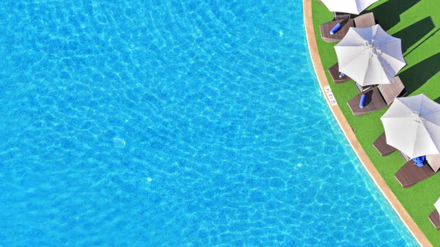 aerial view background texture of blue water shining in the pool on a sunny day. - chair stock videos & royalty-free footage
