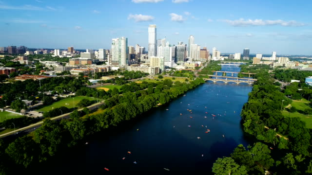 long version - aerial view backing up away from austin downtown skyline cityscape 2019 with kayakers - austin texas stock videos & royalty-free footage