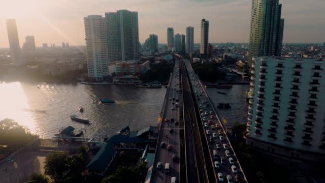 vidéos et rushes de vue aérienne de coucher de soleil au bord de la rivière de bkk - transport aérien