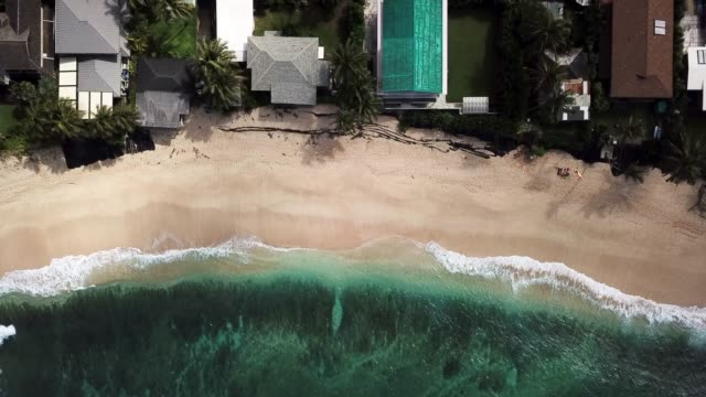 aerial view: beachfront property with waves breaking on sandy beach - 泡立つ波点の映像素材/bロール