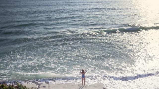 vídeos y material grabado en eventos de stock de ws aerial view, beautiful woman looking at the ocean - traje de baño de una pieza