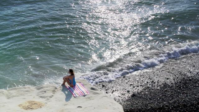 vídeos y material grabado en eventos de stock de ws aerial view, beautiful woman sitting by the ocean - traje de baño de una pieza