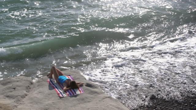 vídeos y material grabado en eventos de stock de ws aerial view, beautiful woman sunbathing by the ocean. - traje de baño de una pieza